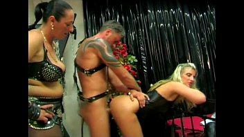 two dominas caning their marionette